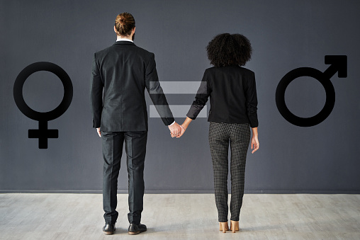Rearview shot of two corporate businesspeople holding hands together in studio with gender symbols inserted in the background